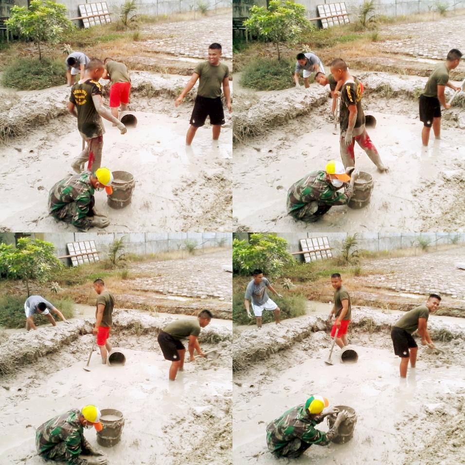 Komandan beserta anggota sedang membersihkan kolam ikan belakang markas.
